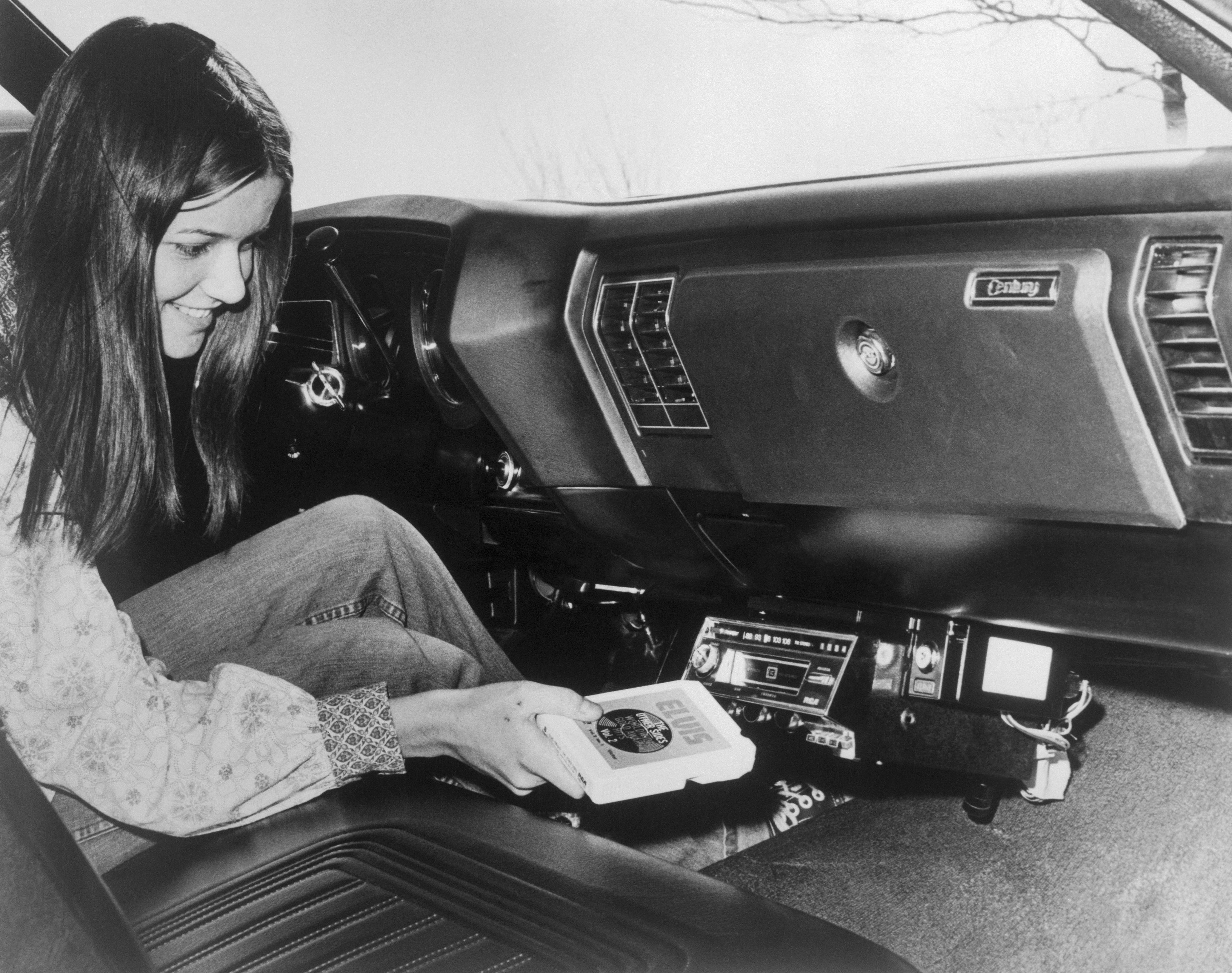 Woman Inserting Eight-Track Tape in Car Stereo