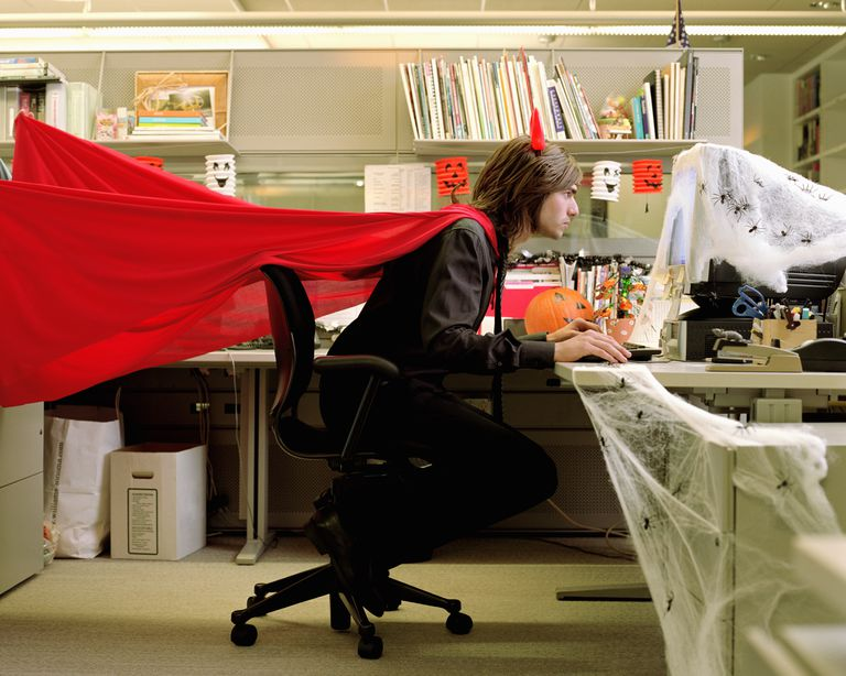 Man wearing devil costume working in cubicle decorated for Halloween