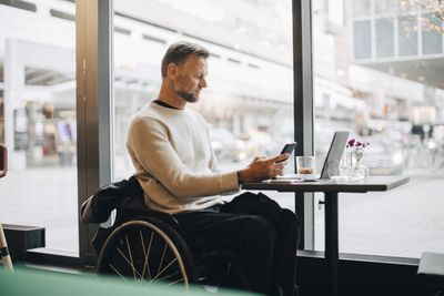 A person in a wheel chair using a smartphone and laptop computer at a cafe.