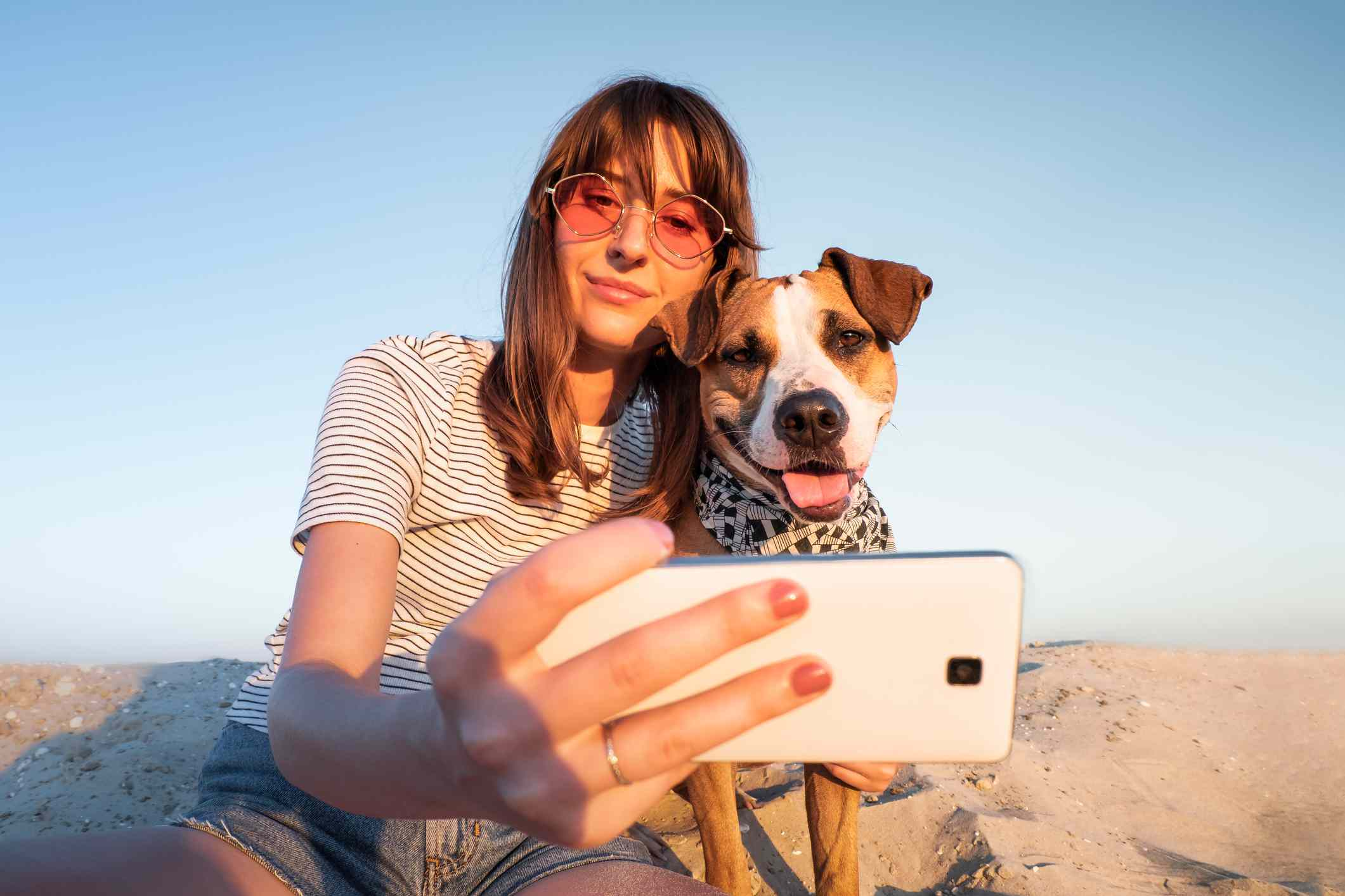 Low Angle View Of Young Woman Taking Selfie With Dog Through Smart Phone At Beach Against Clear Sky