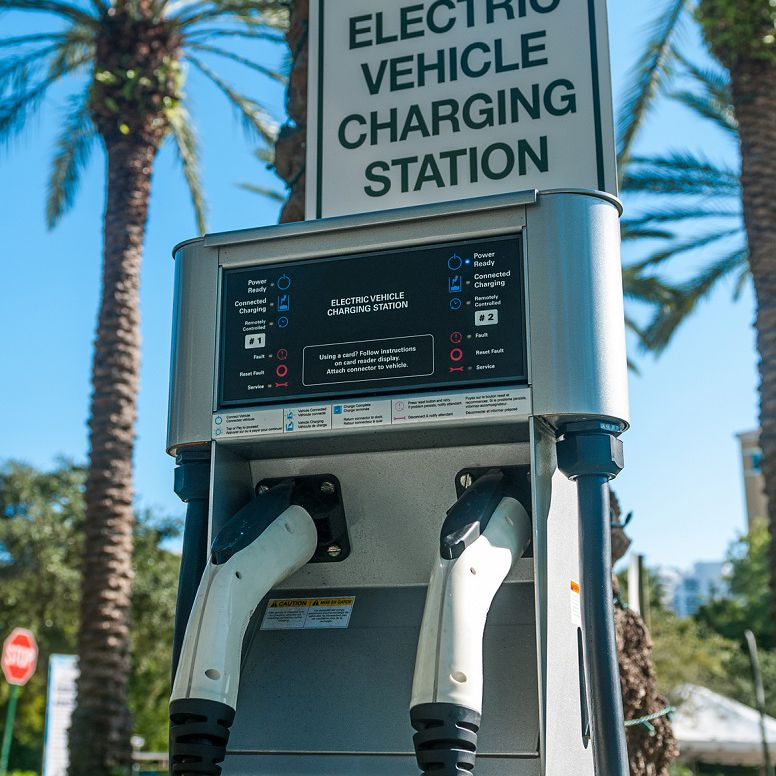 Electric vehicle charging station sign on top of a public charging station with palm trees in background.