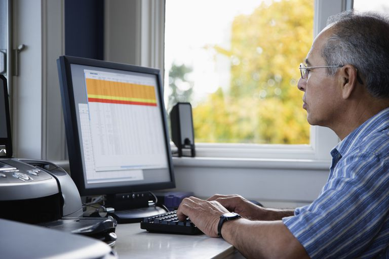 Man on a desktop personal computer looking at a speadsheet