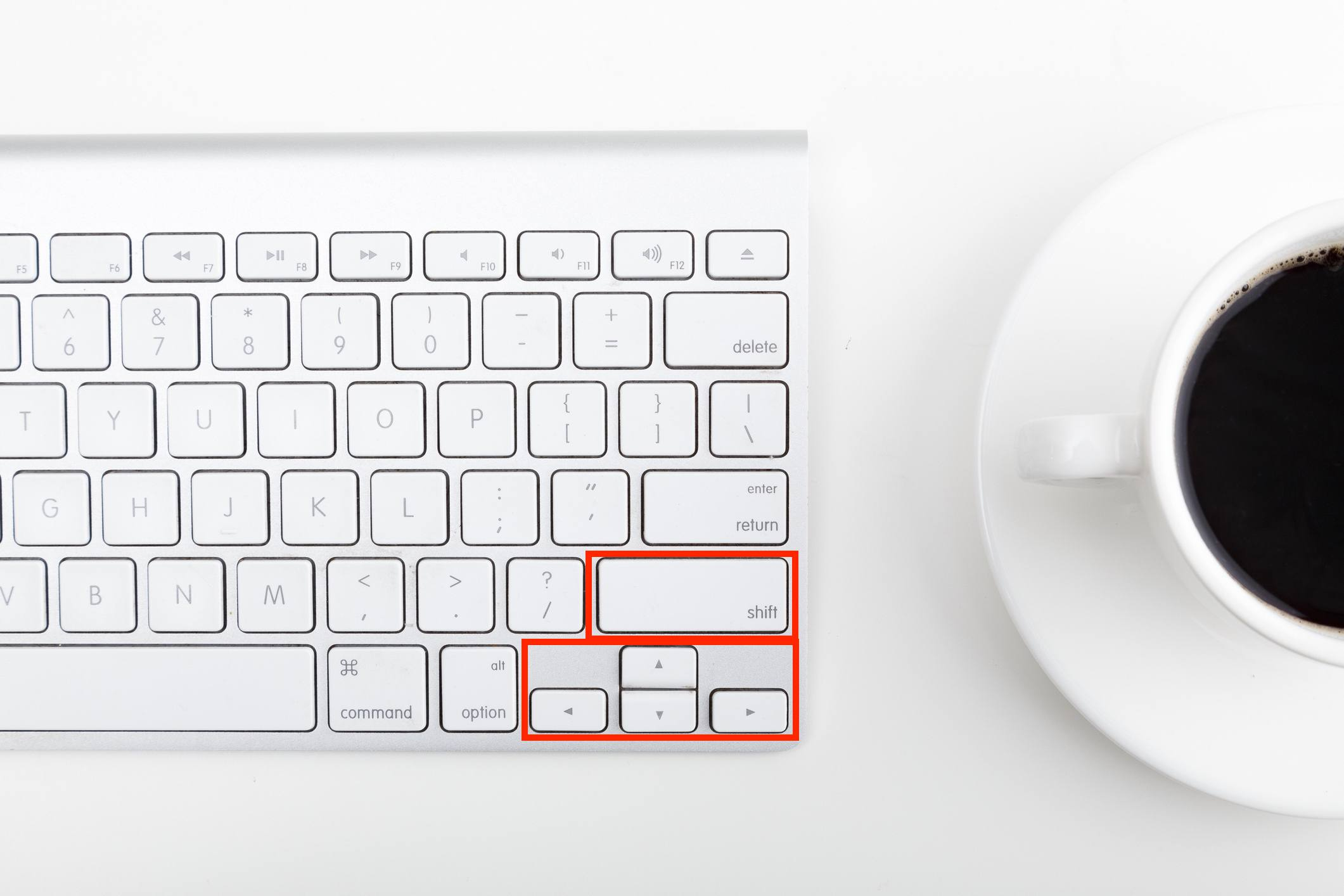 Directly above shot of coffee cup and computer keyboard on table indicating the shift and arrow keys