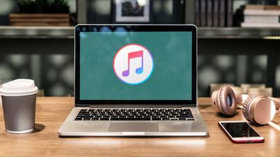 iTunes on laptop screen with coffee and headphones on desk