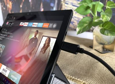 A Surface Pro 7 laptop with an Amazon Fire Stick connected to it via a USB cable on a table with a green cloth and a pot plant.