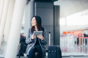 Woman using digital tablet at airport terminal