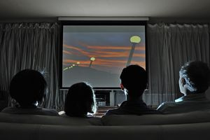 Family watching movie at home on projection screen