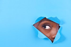 An eye peeking through torn blue paper