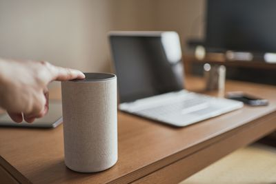 A close up of someone touching a smart speaker near a laptop