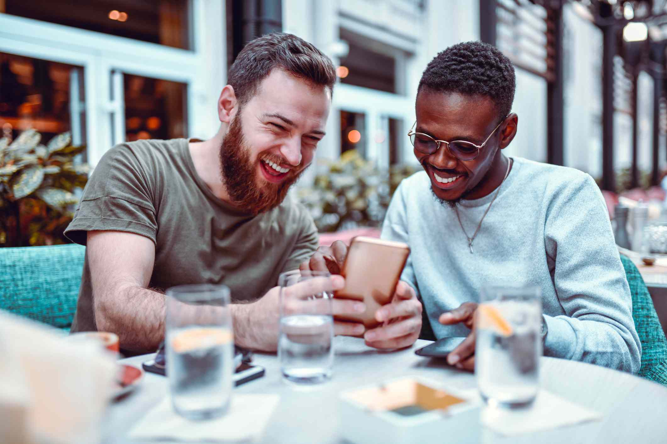Two male friends laughing while looking at Facebook on an iPhone at a cafe