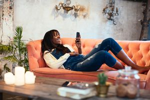 Laughing woman lying on the couch at home using cell phone