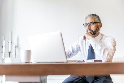 College professor using laptop at a desk
