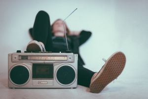 person laying on bed next to a gray radio