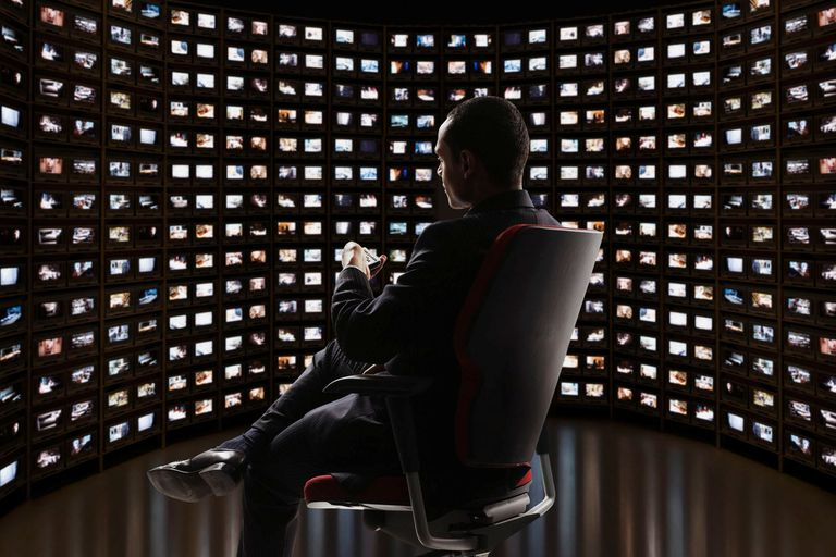Man sitting in chair in front of a semi circle of video monitors