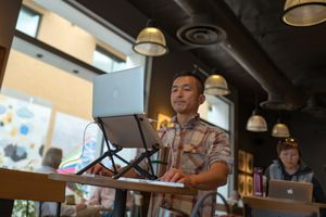 Presentation designer using a laptop camera to record video.