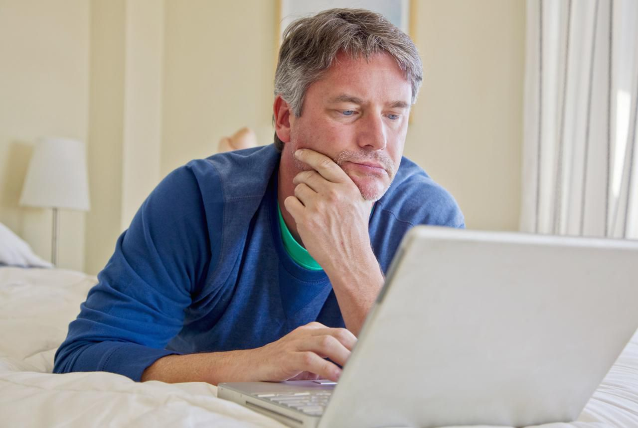 Man on computer in bed room