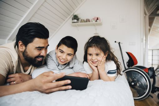 A man and his two children lie on a bed watching a smartphone and smiling