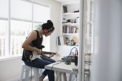Musician playing electric guitar, recording music in home office