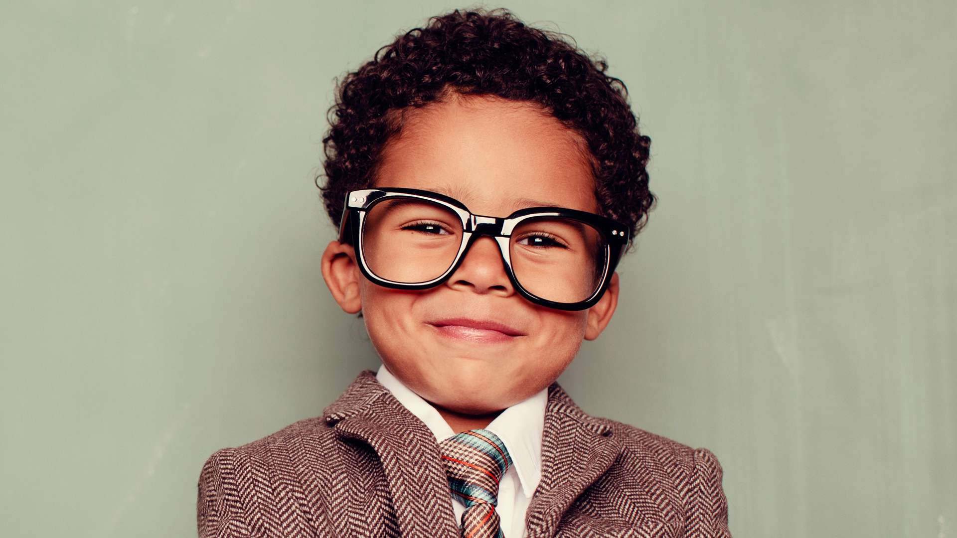 A young boy with glasses and a suit.