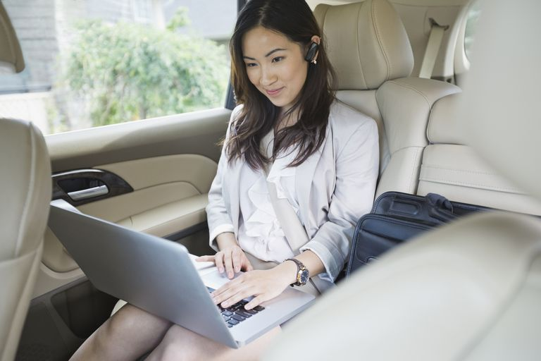 Woman using laptop in car with Bluetooth headset