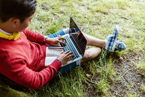 Student sitting against tree with computer and notebook