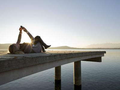 A woman lying on a dock as the sun goes down, looking at her phone