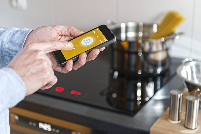 Man controlling smart oven and smart stove with smartphone.
