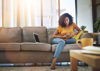 Homeowner using a phone sitting on couch next to computer
