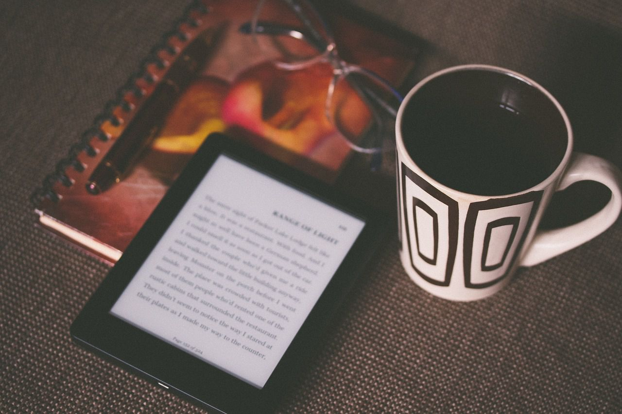 Picture of an ebook, a drink, a notebook, and a pair of glasses on a table