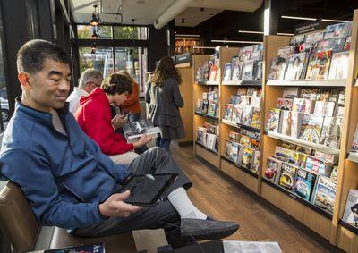 Person holding e-reader, sitting next to magazine rack