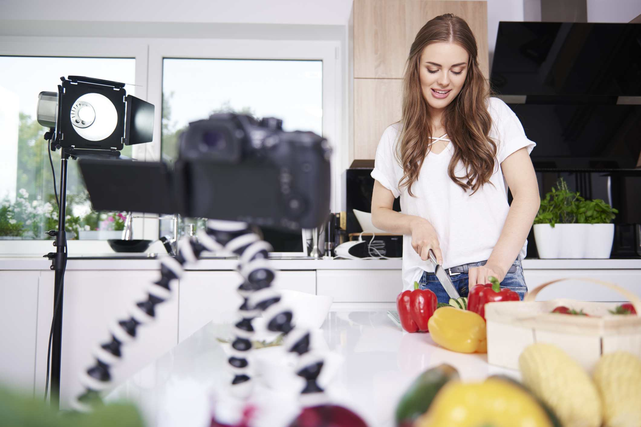 A woman recording a video for YouTube as she cooks a meal in her kitchen.