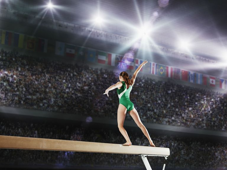 A gymnast performs on the balance beam, a summer olympics event.