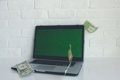 Money flying around a laptop computer