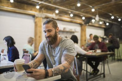 Man using smartphone in busy coffee shop.