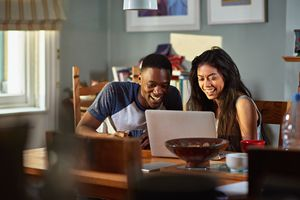 Couple laughing at footage on laptop at breakfast