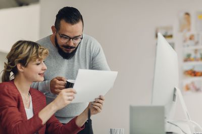 Man and woman looking at piece of paper in an office.