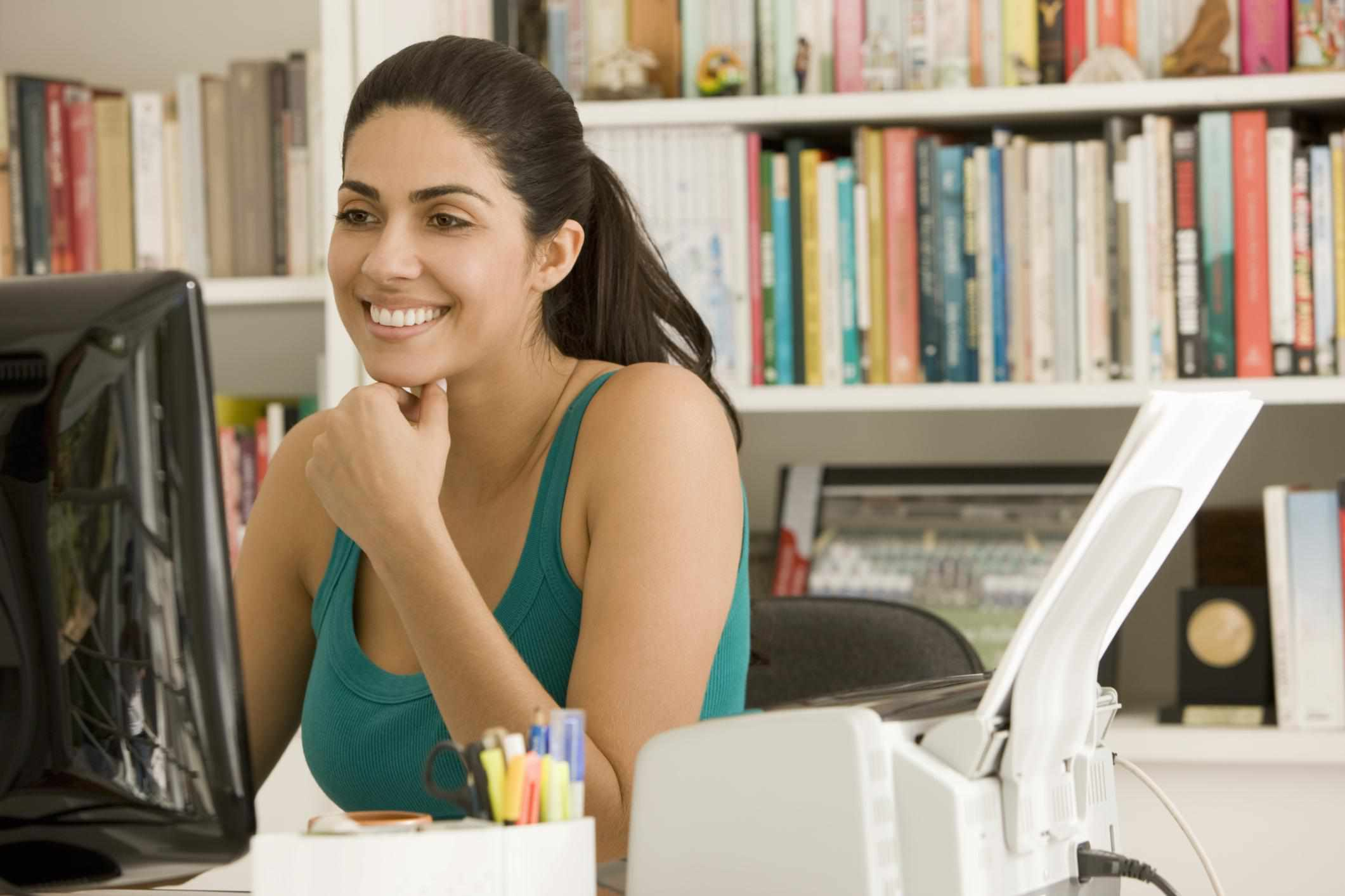 Person sitting at desk, looking at computer, with printer on the side