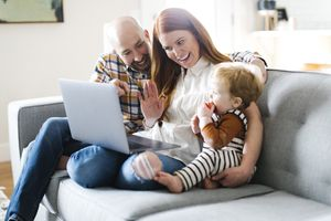 A family including a baby are sitting on a sofa looking at a laptop screen smiling