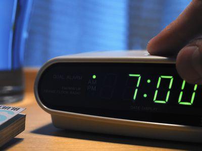A person pressing a button on a digital alarm clock.