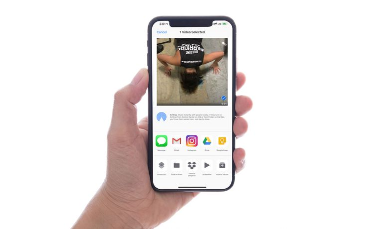 A hand holding an iPhone with a selected video and the share menu.