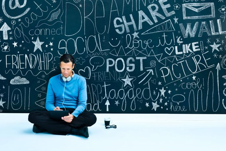 Man sitting in front of wall with social media phrases