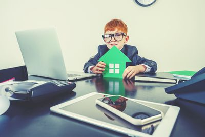 A boy holding a green home cutout to illustrate green tech in the home