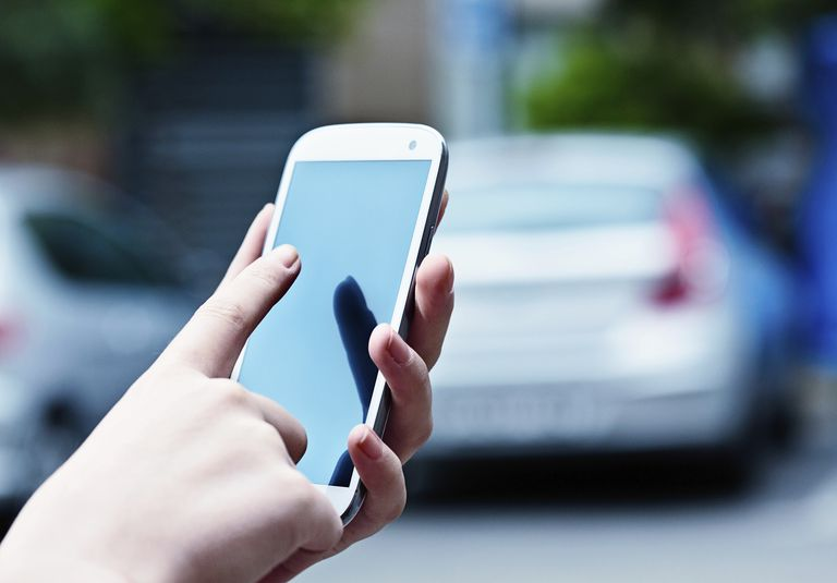 Using phone in a parking lot in front of a car