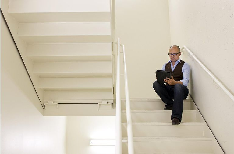 Business man sitting in stairwell using computer