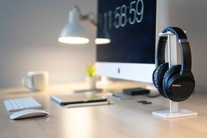 A pair of headphones on a stand along with an iMac on a desk.