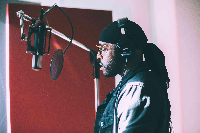 Someone recording voice audio in a studio.