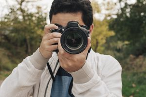Man taking a picture with lens toward the camera