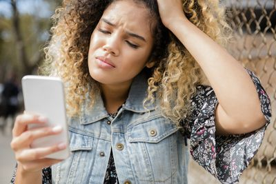 Person holding smartphone with frustrated look and hand on head