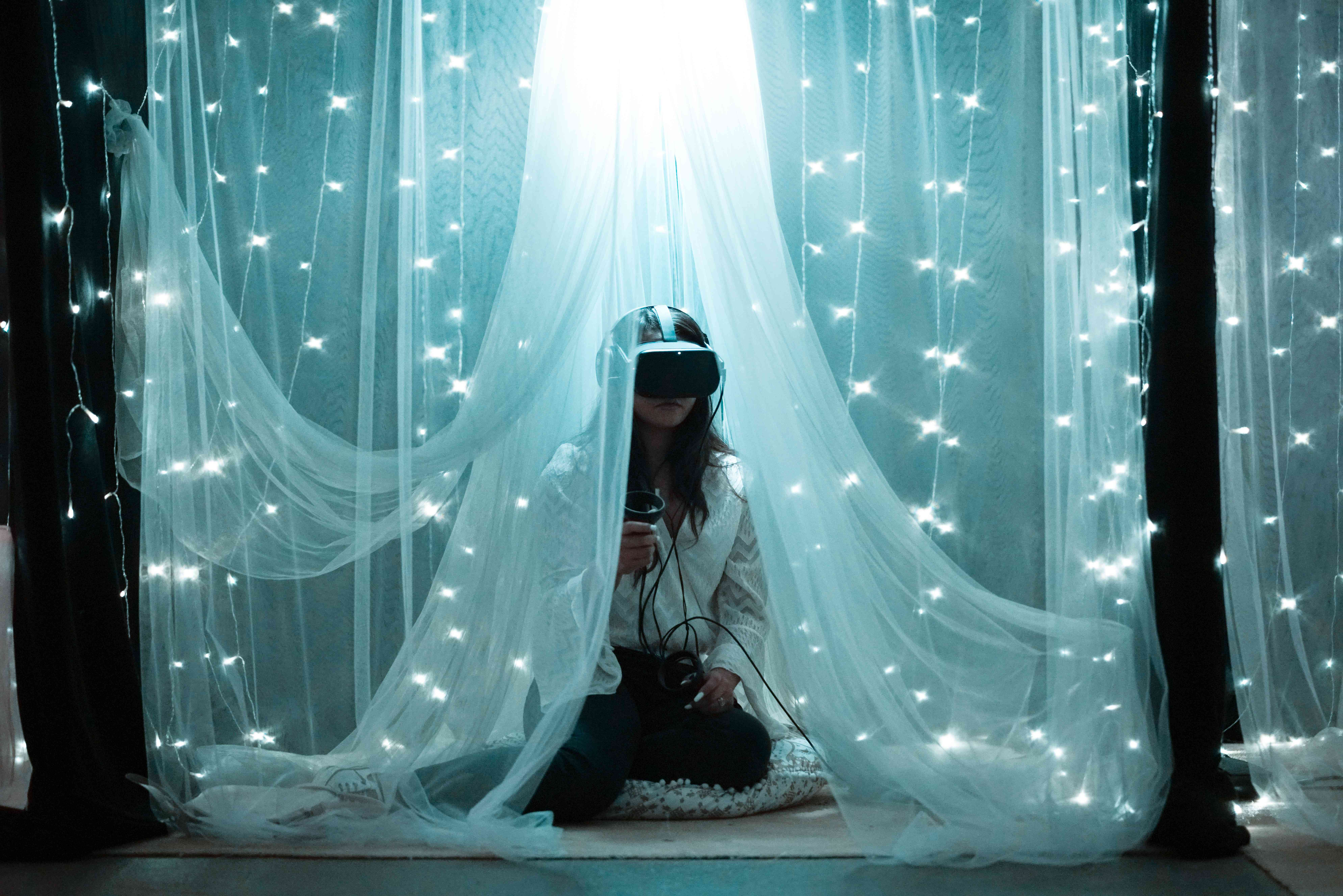 Someone sitting under a curtain of lights using a VR headset and controls.