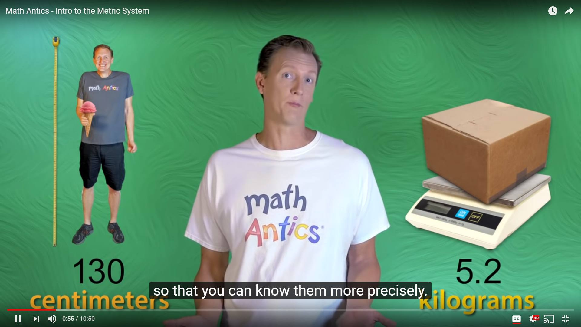 Man talking about measurement units in front of a screen with a man next to a tape measure and a box on a scale
